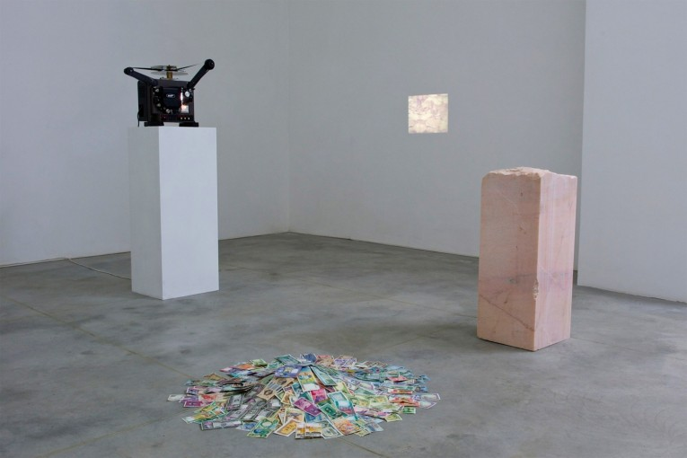 Imperial Stone, 2010, marble, 16 mm film, Eiki projector, old currencies; installation view at Monitor, Rome